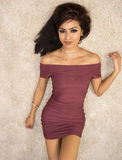 Beautiful elegant woman wearing burgundy dress. Lying on rug looking up Royalty Free Stock Image
