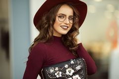 Beautiful elegant woman is wearing fashion autumn clothes and glasses with black bag, fall concept Stock Image