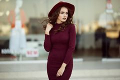 Portrait of beautiful elegant woman is wearing fashion autumn red clothes infront of shop-window Stock Photo