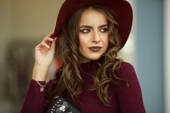 Portrait of beautiful elegant woman is wearing fashion autumn red clothes and hat infront of shop-window Stock Photo