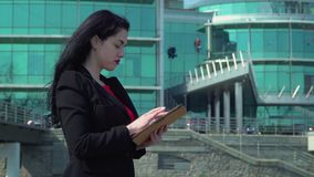Elegant woman in red dress using digital tablet at business center background. Beautiful elegant woman wearing red dress using herdigital tablet at office center stock footage