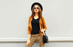 Beautiful elegant woman wearing a retro elegant hat, sunglasses, brown jacket and black handbag. Over grey background royalty free stock photo