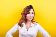 Beautiful elegant woman in white shirt on yellow background. In studio photo Stock Photography