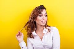 Beautiful elegant woman in white shirt on yellow background. In studio photo Royalty Free Stock Photo
