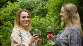 Beautiful elegant women drink red wine, enjoying the holiday of being in a beautiful summer garden with blooming peonies. Slow motion stock footage