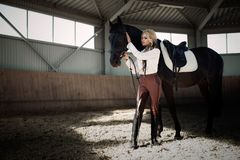 Beautiful elegant young blonde girl standing near her horse dressing uniform competition. Beautiful elegant young blonde girl standing near her black horse Royalty Free Stock Photos