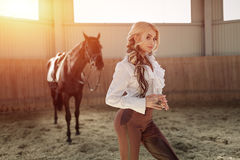 Beautiful elegant young blonde girl standing near her horse dressing uniform competition Royalty Free Stock Image