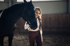 Beautiful elegant young blonde girl standing near her horse dressing uniform competition Royalty Free Stock Photography