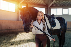 Beautiful elegant young blonde girl standing near her horse dressing uniform competition Royalty Free Stock Photo