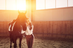 Beautiful elegant young blonde girl standing near her horse dressing uniform competition Stock Photography