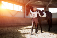 Beautiful elegant young blonde girl standing near her horse dressing uniform competition Stock Photos