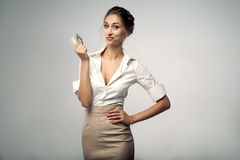 Beautiful elegant young bussines woman standing on the studio with gray background. Holds in his hand a few dollars. and smiling. She dressed in white shirt Stock Images