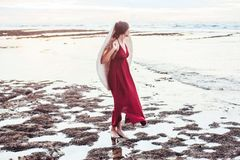 Elegant lady in straw hat and red dress on beach royalty free stock image