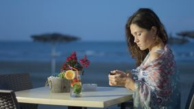 Beautiful elegant young lady typing message on smartphone, relax at beach cafe. Stock footage stock footage