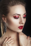 Beautiful elegant young model with red lips and color evening make-up.Woman Face on dark background.Picture taken in the studio Stock Photos
