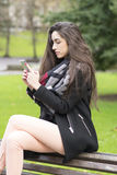 Beautiful elegant young woman using smart phone in the park. Royalty Free Stock Photos