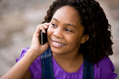 Beautiful elementary age girl on cellphone Royalty Free Stock Images