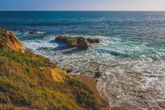 Laguna Beach Rock Formations. Beautiful elevated view of Laguna Beach on a sunny day with stunning blue water and waves crashing into rock formations, Laguna Royalty Free Stock Image