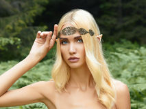 Beautiful elf girl. Fantasy young woman in woods stock photo