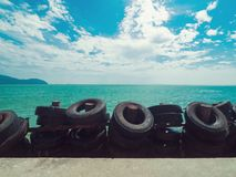Beautiful emerald green sea and blue sky. With sea wave protection made from old tire on the beach Royalty Free Stock Photo