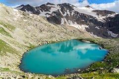 Beautiful emerald mountains lake. Amazing emerald mountains lake among rocks reflecting snow peaks Royalty Free Stock Photography