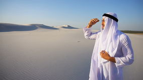 Beautiful Emirate Sheikh looks out in distance caravan of camels, standing among wide desert on hot day. Serious young Arabian UAE Sheikh man peers into stock video
