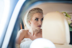 Beautiful emotional blonde bride posing in luxury car, face clos Stock Photography