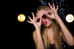 Beautiful emotional blonde in a nightclub at disco. Girl playfully hamming in a disco in a nightclub Stock Photo