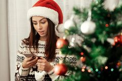 Beautiful emotional brunette woman in red santa hat and reindeer Royalty Free Stock Photography