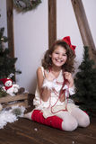 Beautiful emotional girl. In a home studio for the New Year and Christmas. In a white dress with a red bow and  socks Stock Photos