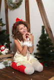 Beautiful emotional girl. In a home studio for the New Year and Christmas. In a white dress with a red bow and  socks Royalty Free Stock Images