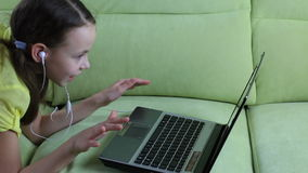 Beautiful emotional girl listening to song on laptop and sings stock footage