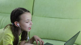 Beautiful emotional girl listening to song on laptop and sings. stock video