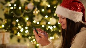Beautiful Emotional Girl in Santa Hat using Gadget Next to Christmas Tree. Smiling Woman with Smartphone at Xmas stock video footage