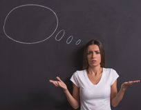 Beautiful emotional lady. Beautiful confused young girl is lifting her hands in dismay and looking at camera, standing against blackboard with drawn speech stock image