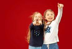 Beautiful emotional little girls isolated on red background stock photography