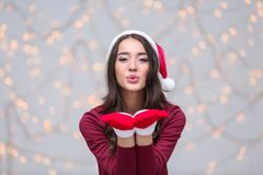 Beautiful emotional woman in Christmas hat and red winter gloves Stock Photos