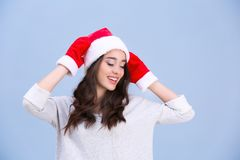 Beautiful emotional woman in Christmas hat and red winter gloves Royalty Free Stock Photo