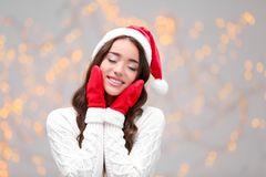 Beautiful emotional woman in Christmas hat and red winter gloves Royalty Free Stock Images