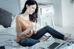 Beautiful emotional woman crumpling paper. Creativity crisis. Beautiful nice emotional woman sitting on the bed and crumpling paper while looking for new ideas Royalty Free Stock Photo