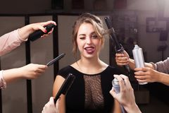 Grimacing girl surrounded by hands with makeup products stock photography