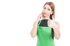 Beautiful employee calling someone and showing thumbup Royalty Free Stock Photography