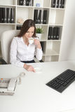 The beautiful employee has coffee in a workplace Royalty Free Stock Photography