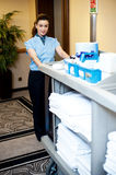 Beautiful employee psuhing housekeeping cart. To deliver the toiletries Royalty Free Stock Photography