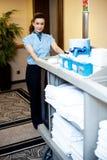 Beautiful employee psuhing housekeeping cart Royalty Free Stock Photography