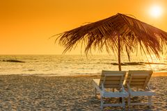 Beautiful empty beach and a pair of sun loungers. Tinted royalty free stock photo
