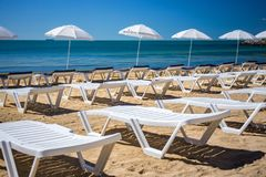 Beautiful empty beach with rows of sun beds under straw umbrellas Royalty Free Stock Photo