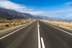Beautiful empty road in a blue sky day - northern of Chile. South America Stock Photos