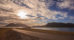 Beautiful empty road bridge leading to mountain with colorful cloudscape in Iceland Royalty Free Stock Images