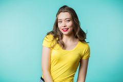 Beautiful energetic young woman smiling on blue background. Positive emotions, happiness stock images